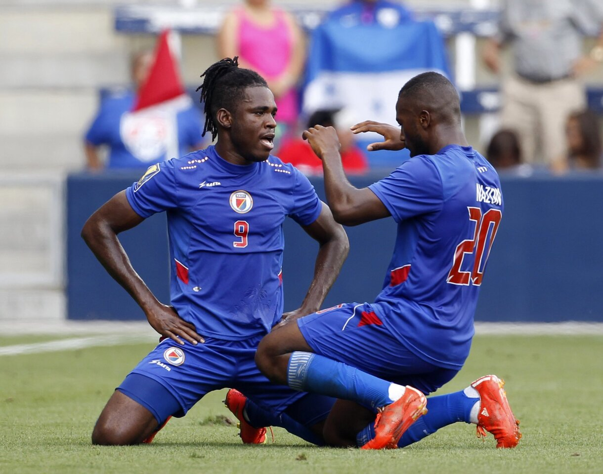 Haiti's Kervens Belfort (9) is congratulated by Duckens Nazon (20) after a goal against Honduras during the first half of a CONCACAF Gold Cup soccer match, Monday, July. 13, 2015, in Kansas City, Kan. Nazon scored off a header from Belfort. (AP Photo/Colin E. Braley)
