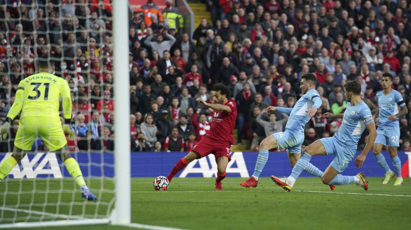 Liverpool's Mohamed Salah scores his side's second goal during the English Premier League soccer match between Liverpool and Manchester City at Anfield, Liverpool, England, Sunday Oct. 3, 2021. (Peter Byrne/PA via AP)
