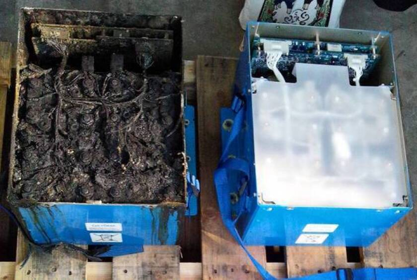 The damaged main lithium-ion battery, left, from the All Nippon Airways plane that made an emergency landing in Japan on Jan. 16 contrasts with the plane's undamaged auxiliary battery.