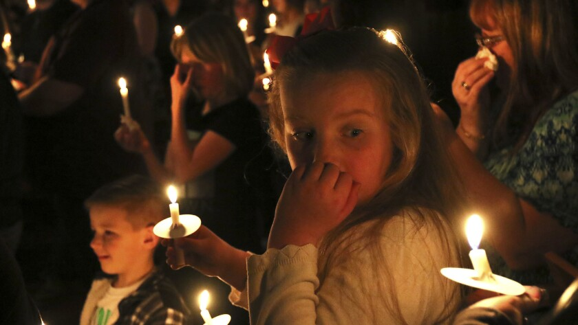 Alyssa Bell, 9, of Riddle, Ore., participates in a vigil for the victims of a house fire on March 1.