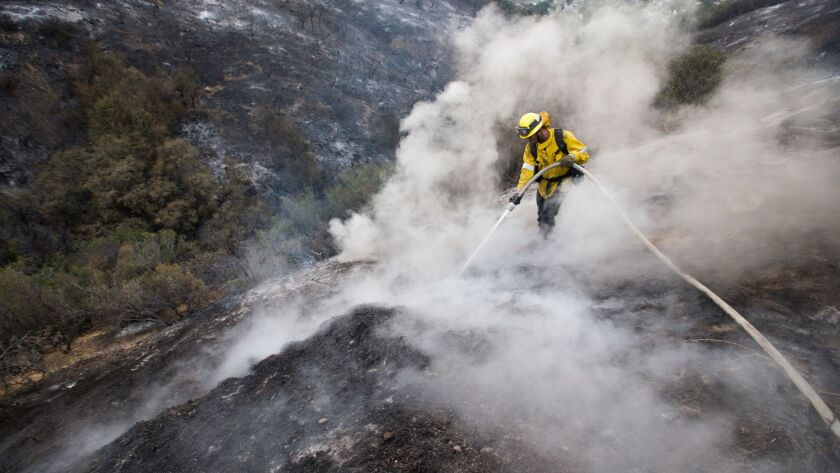 L.A. County firefighter Kevin Sleight extinguishes hot spots while battling the La Tuna fire along Crestline Drive in Los Angeles on Sunday.