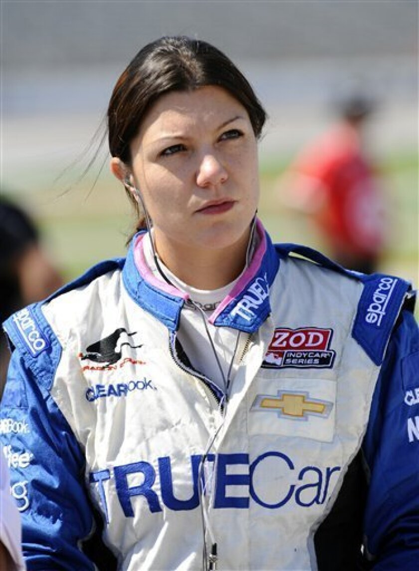FILE - In this June 8, 2012, file photo, driver Katherine Legge watches before IndyCar Series qualifying at Texas Motor Speedway in Fort Worth, Texas. Legge has threatened legal action over her termination from Dragon Racing on Wednesday, Feb. 13, 2013, one day after the team said Sebastian Saavedr