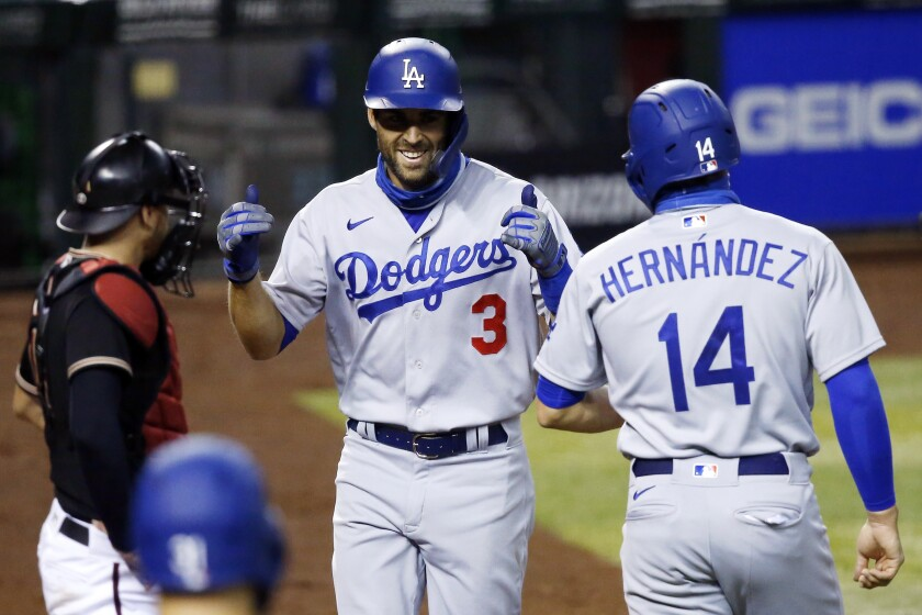 Los Angeles Dodgers' Chris Taylor (3) smiles as he celebrates his three-run home run against the Arizona Diamondbacks with teammate Kiké Hernandez (14) as Diamondbacks catcher Carson Kelly, left, looks to the dugout during the eighth inning of a baseball game Saturday, Aug. 1, 2020, in Phoenix. (AP Photo/Ross D. Franklin)