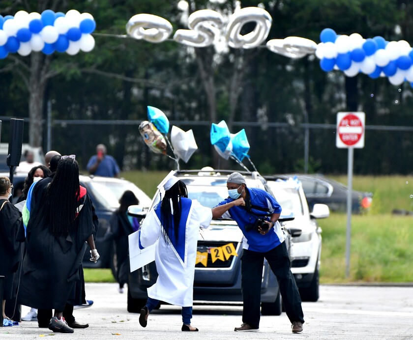 A drive-through high school graduation in College Park, Ga. Schools are wrestling with how to approach the new school year.