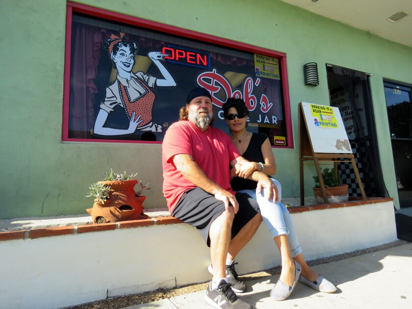 Steve and Deb Berry sit outside Deby's Cookie Jar. Both are business owners who paid fees to fund a business improvement district in Imperial Beach.