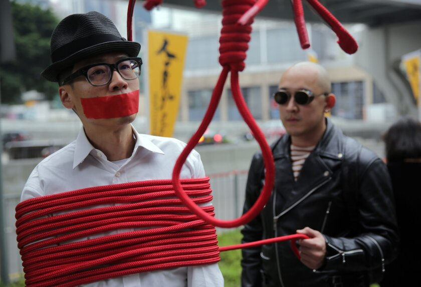 A protester is wrapped up with a rope made into a noose during a Jan. 10 march in Hong Kong calling for the release of missing booksellers from the Mighty Current publishing house.