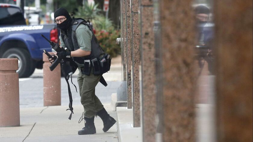 An armed shooter stands near the Earle Cabell Federal Building Monday, June 17, 2019, in downtown Da