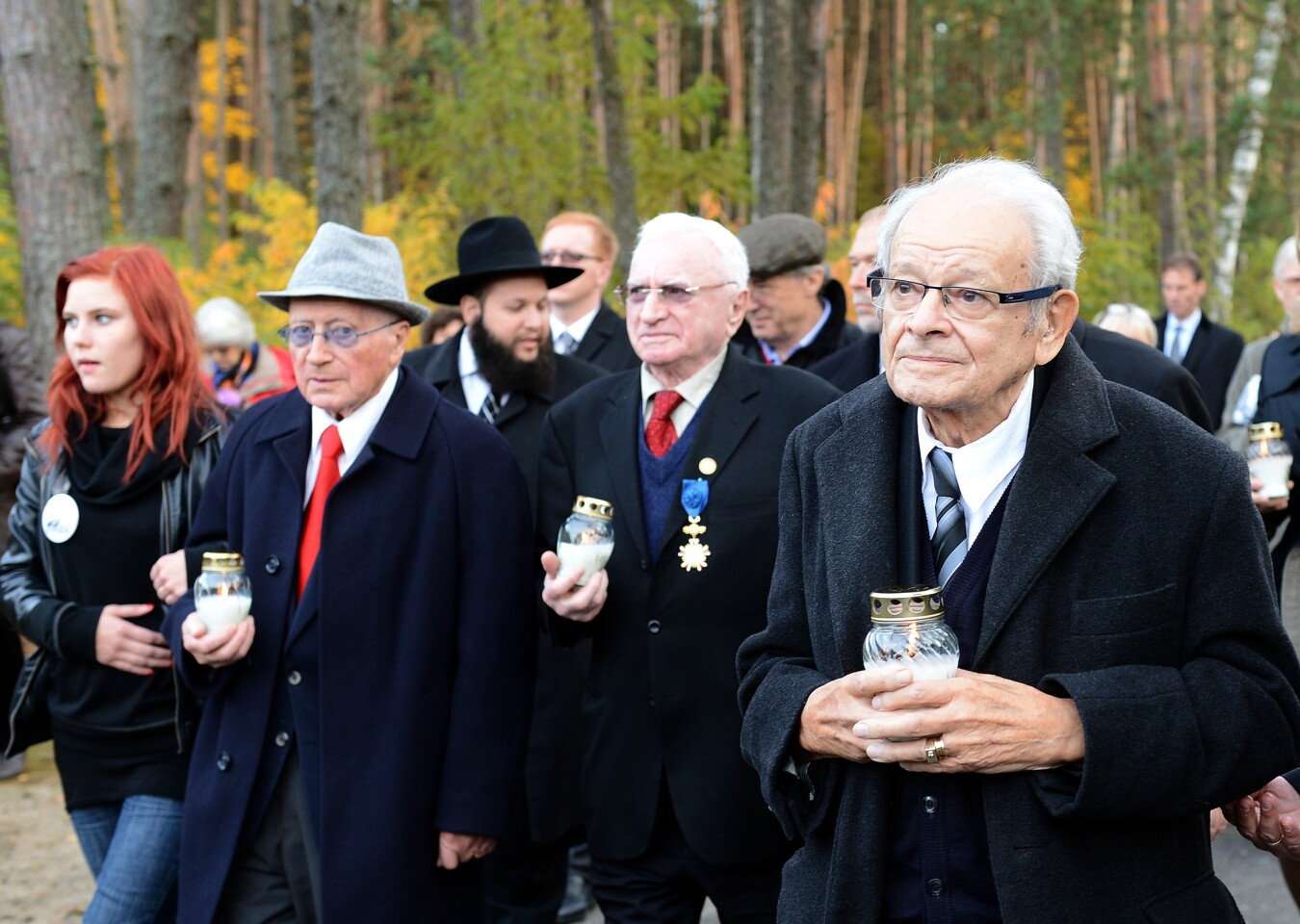 During a 2013 ceremony commemorating the 70th anniversary of a successful uprising at the Sobibor camp, insurgents Philip Bialowitz, from left, Thomas Blatt and Jules Schelvis light candles.