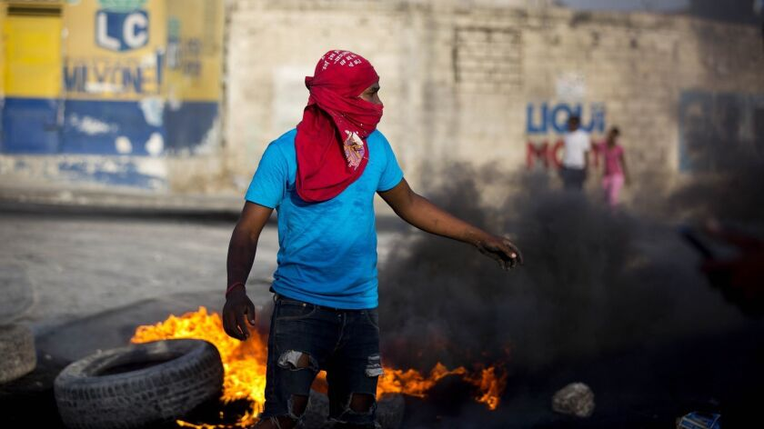 A masked protester sets up a barricade in the middle of the street July 7 in Port-au-Prince, Haiti. Thousands took to the streets after the government announced a sharp increase in gasoline prices.