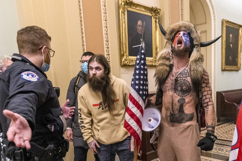 FILE - In this Jan. 6, 2021, file photo, is Jacob Chansley, right with fur hat, during the Capitol riot in Washington. Chansley pleaded guilty on Friday, Sept. 3, 2021, to a felony obstruction charge. He carried a flagpole topped with a spear into the insurrection, yelled into a bullhorn as officers tried to control the crowd, posed for photos on the Senate dais and wrote a note to then-Vice President Mike Pence that prosecutors have said was threatening. (AP Photo/Manuel Balce Ceneta, File)