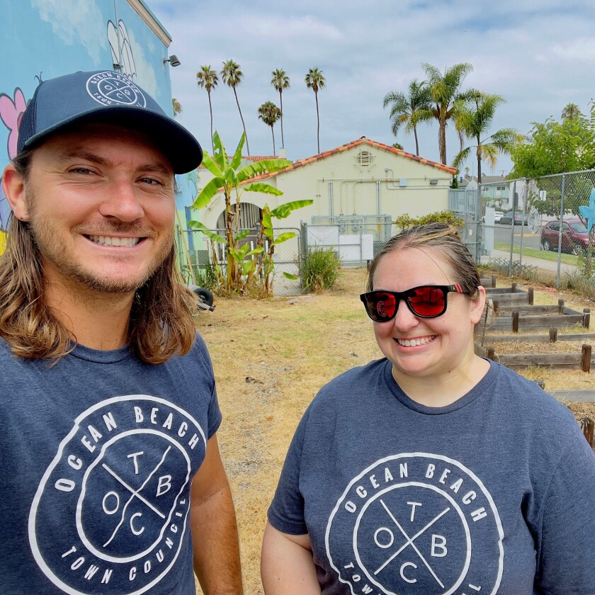 Ocean Beach Town Council members Cameron Reid and Stephanie Logan clean up the Ocean Beach Elementary School grounds Aug. 21.
