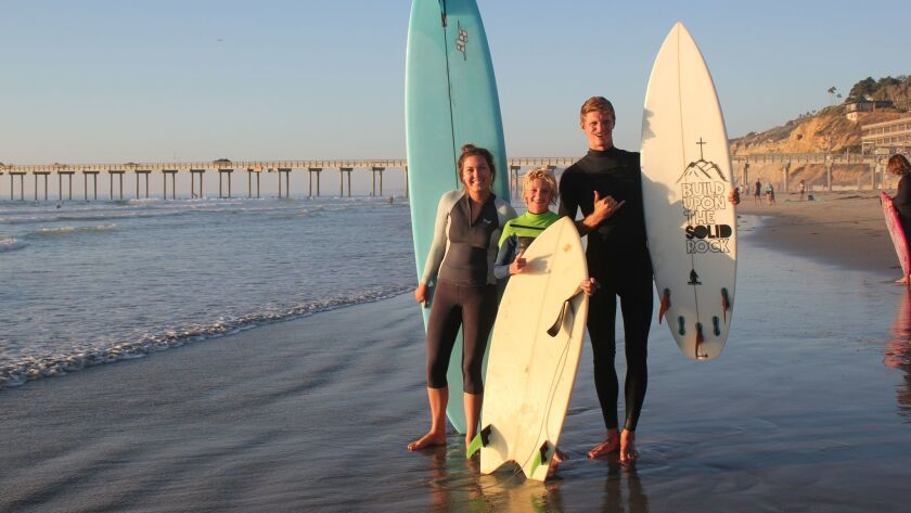 Surf Church members Rebecca Mueller, Jacob Kelly and Alex Reynolds at Scripps Pier, Sept. 29