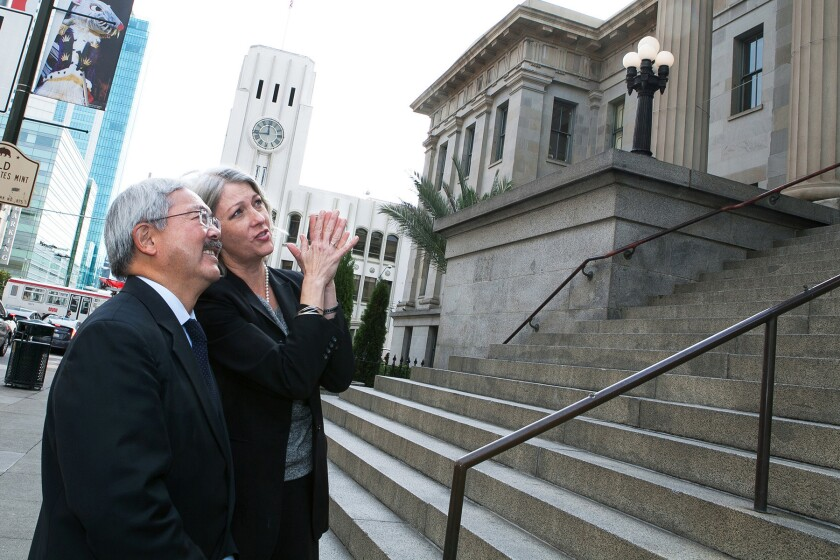 San Francisco Mayor Ed Lee looks on at the front of the Old U.S. Mint as Anthea Hartig, executive director of the California Historical Society, describes architectural details.