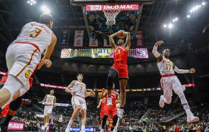 El jugador OG Anunoby (c) de los Toronto Raptors en acción contra Marco Belinelli (i) y Dennis Schroeder (d) de los Atlanta Hawks durante el partido de baloncesto de la NBA entre los Toronto Raptors y los Atlanta Hawks que se disputa en el Philips Arena en Atlanta, Georgia (EE. UU.). EFE