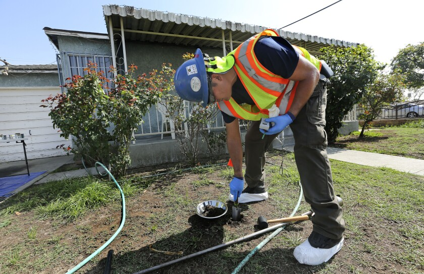 Glen Van Eekout, an environmental health specialist for the L.A. County health department, collects a soil sample from the front yard of a home in Commerce.