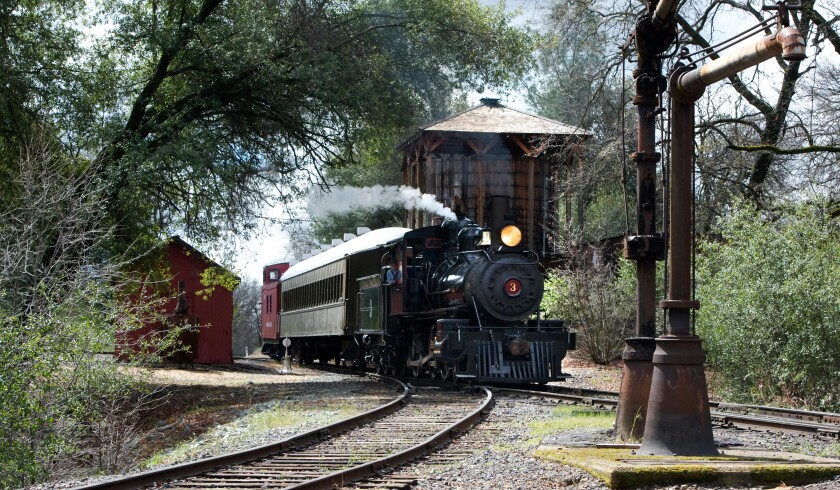 Steam engine No. 3 carries riders past a water tank as it returns to the station at historic Railtown 1897 State Park in Jamestown, Calif.