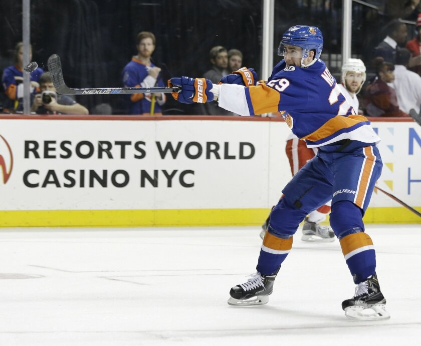 New York Islanders' Brock Nelson hits the puck in the air just before scoring during the second period of an NHL hockey game against the against the Detroit Red Wings, Monday, Feb. 15, 2016, in New York. (AP Photo/Seth Wenig)