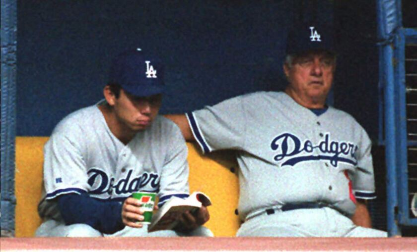 Dodgers pitcher Hideo Nomo reads a book as manager Tom Lasorda watches a 1995 game in Montreal.