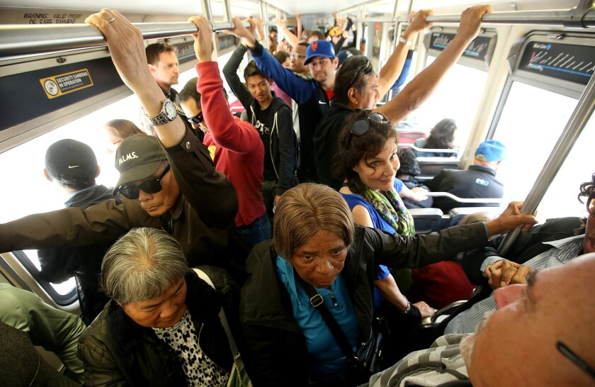 Riders experience cramped conditions during the first day of Expo Line trains running to Santa Monica, on Friday, May 20.