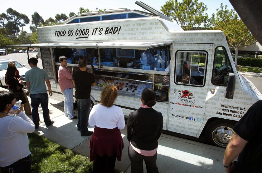 Customers wait for orders at the Devilicious food truck during a lunch stop in Mira Mesa on Wednesday, Sept. 21, 2011.
