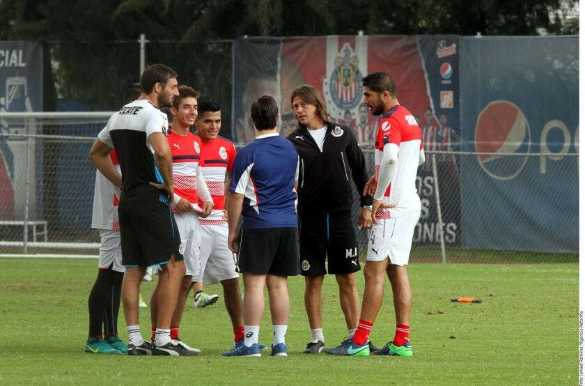 El entrenador Matías Almeyda (de negro), dialoga con jugadores de las Chivas.