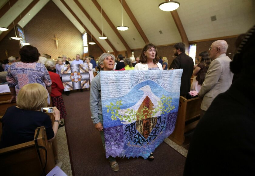 Parishioners carry quilts made to commemorate a vigil at the St. Frances X. Cabrini Church at the conclusion of a planned final service at the church, Sunday, May 29, 2016, in Scituate, Mass. For more than 11 years, a core group of about 100 die-hard parishioners at the church have kept their paris