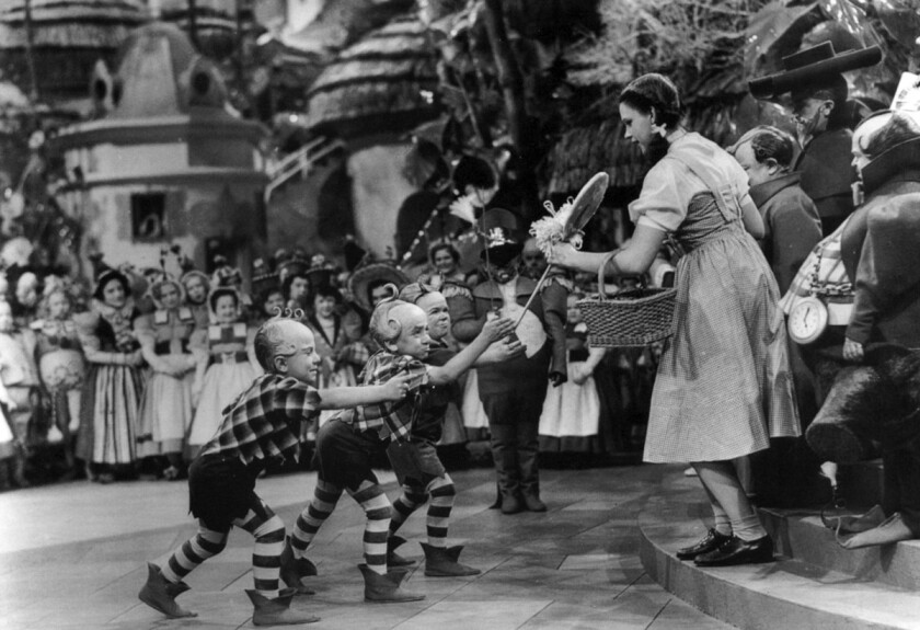 "Jerry Maren presents Judy Garland with a lollipop in the film ""The Wizard of Oz."""