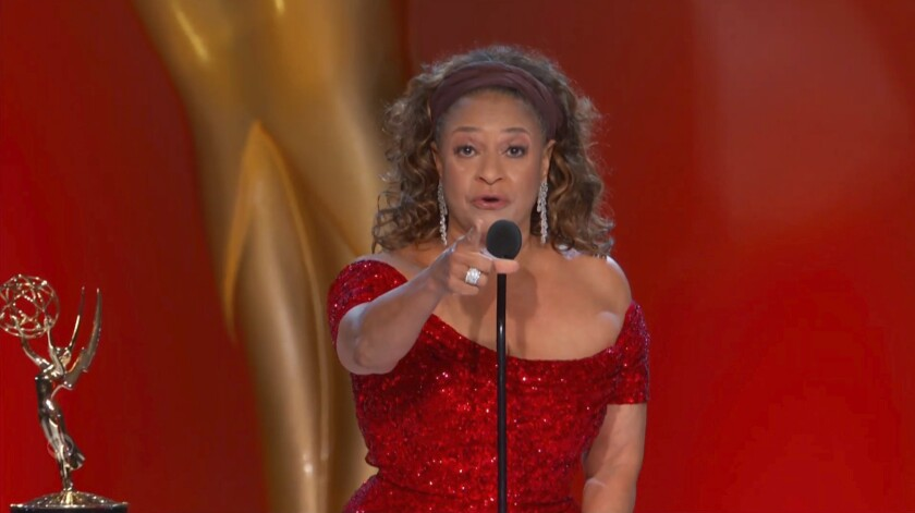 Debbie Allen, in a sparkly red dress, speaks into a microphone and points to her audience