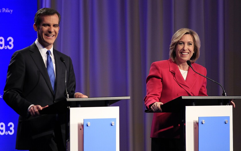Los Angeles mayoral candidates Eric Garcetti and Wendy Greuel chat before they square off in a debate at USC's Health Sciences Campus in April.