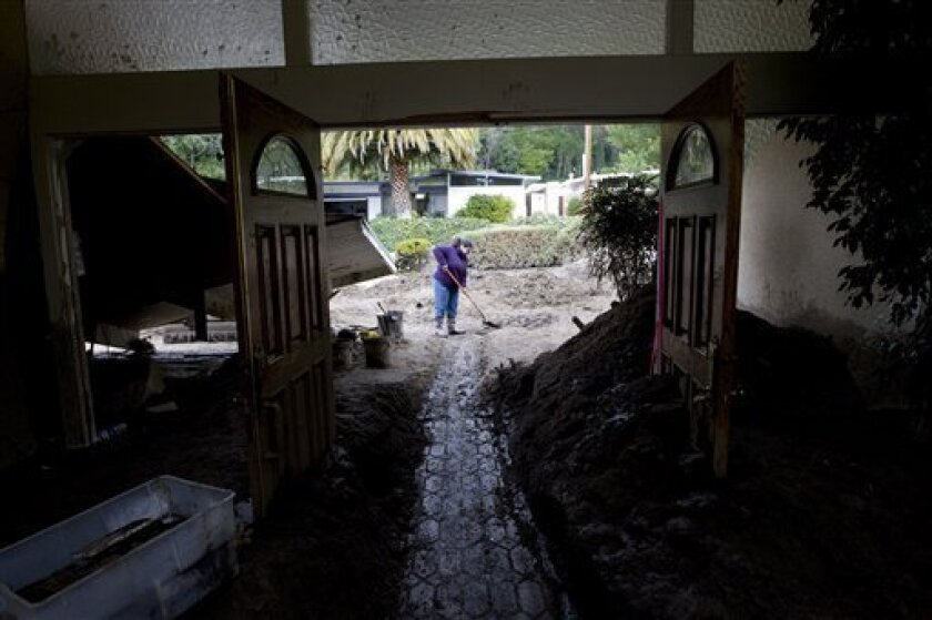 Catherine Markgraf shovels mud from the entrance of her property after a mudslide in La Canada Flintridge, Calif. on Monday, Feb. 8, 2010. Another storm is expected to hit the Los Angeles area Tuesday. (AP Photo/Hector Mata)
