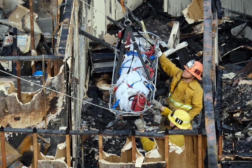ARCHIVO. Dos bomberos ayudan en conducir un cuerpo hacia arriba a medida que lo levanta un camión de bomberos con escalera, dentro de las ruinas de un edificio de oficinas abandonado en el distrito Westlake justo al oeste del centro de Los Ángeles, el martes 14 de junio de 2016, por lo que ya suman cinco muertos. Dos hombres y dos mujeres fueron hallados el martes tras utilizar perros especializados en localizar cadáveres. (AP foto/Richard Vogel)