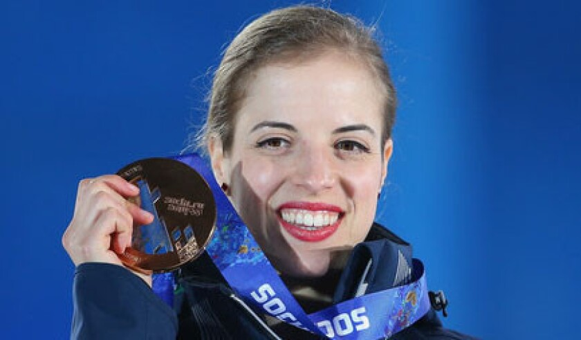 Italian figure skater Carolina Kostner holds up her bronze medal during the Sochi 2014 Winter Olympics.