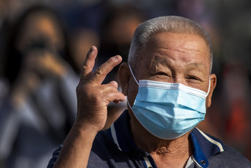 A man gives a hopeful sign after being vaccinated