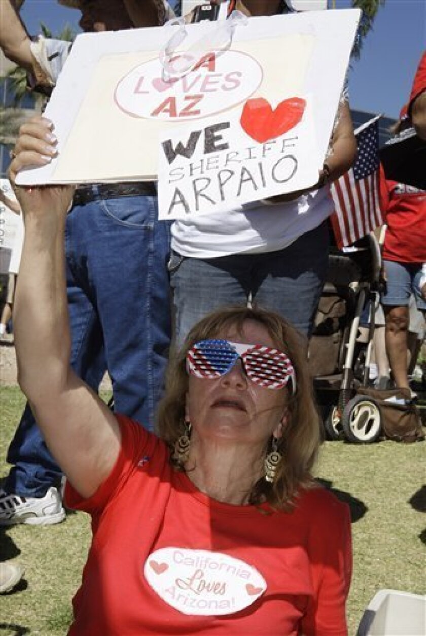 Robin Hvidston, of Upland, Calif., holds up a sign as she joins hundreds at a rally supporting Arizona's new law on illegal immigration as they gather near the capitol Saturday, June 5, 2010, in Phoenix. (AP Photo/Ross D. Franklin)