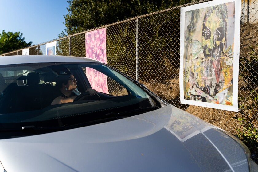 "A driver takes in one of the pieces in Mesa College's drive-thru art exhibition ""Mesa Drive-In,"" on display through Dec. 9."