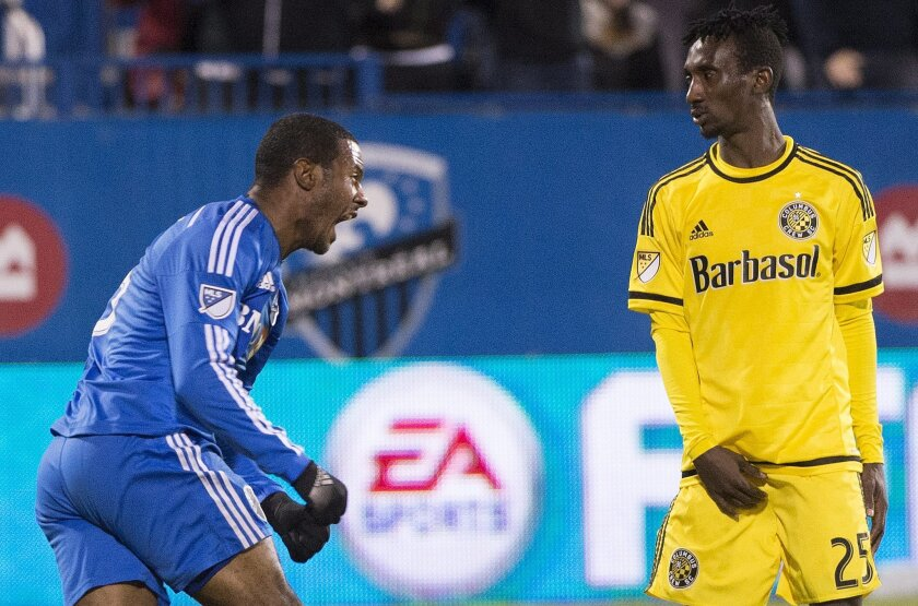Columbus Crew SC 's Harrison Afful, right, looks on as Montreal Impact's Patrice Bernier, left, celebrates after scoring against Columbus Crew SC during first half of an MLS Eastern Conference semi-final first-leg soccer match in Montreal, Sunday, Nov. 1, 2015. (Graham Hughes/The Canadian Press via