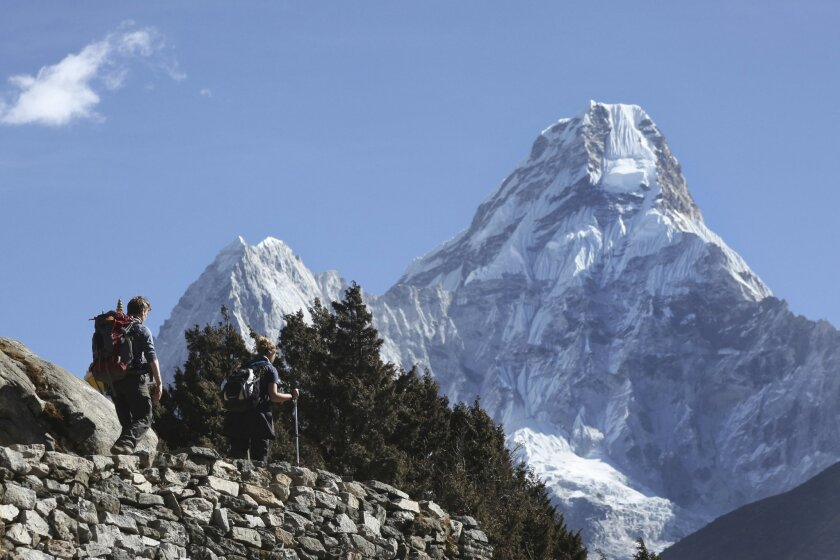 FILE - In this Feb. 19, 2016, file photo, trekkers make their way to Dingboche, a popular Mount Everest base camp, in Pangboche, Nepal. Nepal celebrated Everest Day on Sunday, May 29, 2016, by honoring nine Sherpa guides who fixed ropes and dug the route to the summit so hundreds of climbers could