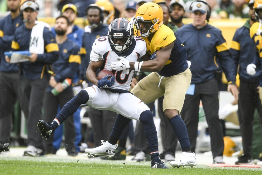 Denver's Emmanuel Sanders is tackled by Green Bay's Adrian Amos on Sunday afternoon.