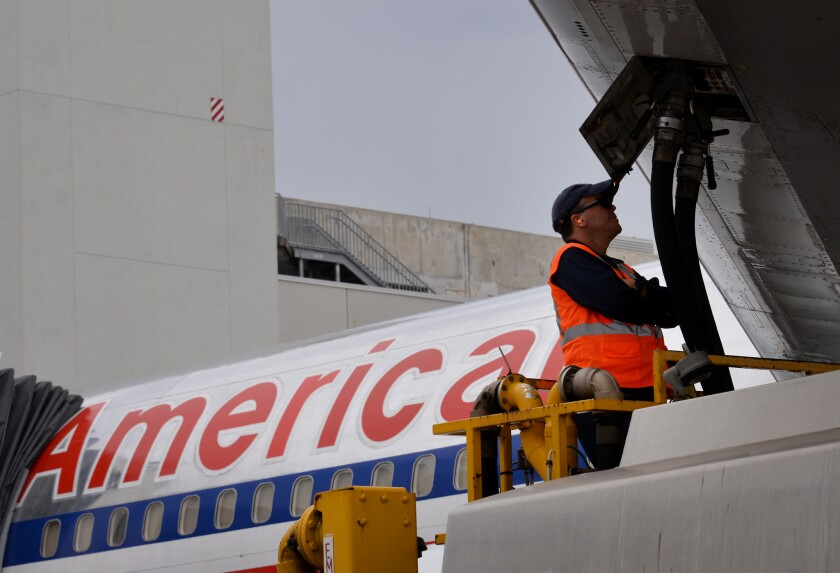 A ground crew worker fuels an American Airlines plane parked at a Miami International Airport terminal. Lower fuel costs are pushing down airfares, according to a new study.