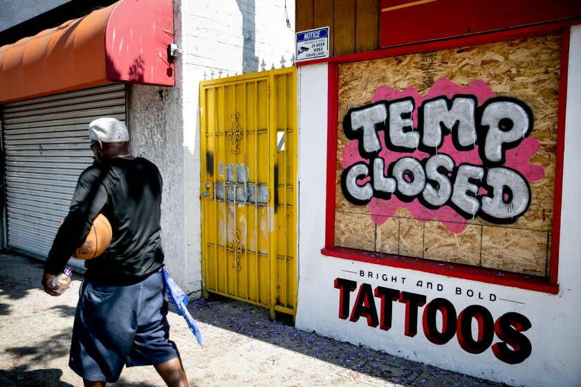 A tattoo parlor on El Cajon Boulevard has its windows boarded up Friday in San Diego.