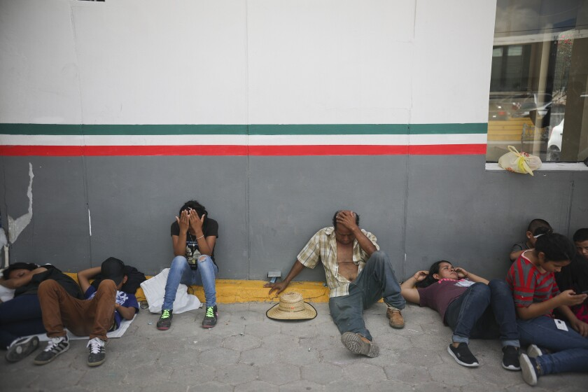 FILE - In this Aug. 1, 2019, file photo, migrants rest near a Mexican immigration center where people have set up a camp to sleep in Matamoros, Mexico, on the border with Brownsville, Texas. An unpublished report says former Homeland Security Secretary Kirstjen Nielsen ordered officers to stop people from stepping on U.S. soil at official crossings with Mexico to claim asylum when she was U.S. Homeland Security secretary, undercutting her public statements at the time that they were welcome to do so. (AP Photo/Emilio Espejel, File)