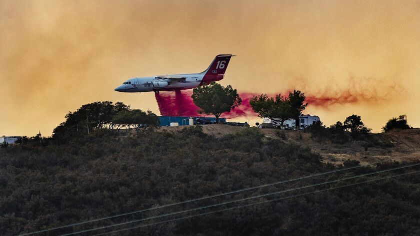 An air tanker flies low to drop fire retardant near campers and trailers on a mountain ridge to fight the Holy fire on Aug. 11, 2018.