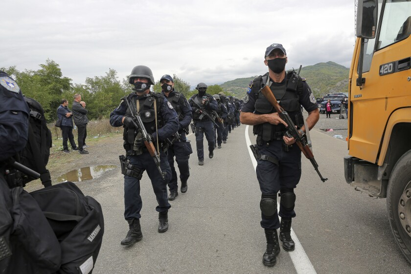Kosovo police officers walk to replace their colleagues near the northern Kosovo border crossing of Jarinje on Tuesday, Sept. 21, 2021. Tensions soared Monday when Kosovo special police with armored vehicles were sent to the border to impose a rule on temporarily replacing Serb license plates from cars while they drive in Kosovo. (AP Photo/Visar Kryeziu)