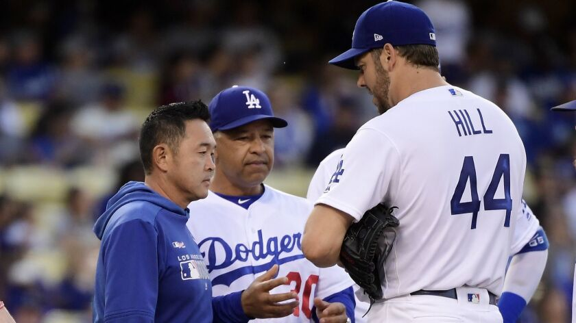 Dodgers pitcher Rich Hill, right, is taken out of the game by manager Dave Roberts, center, due to an injury prior to the second inning against the San Francisco Giants on Wednesday at Dodger Stadium.