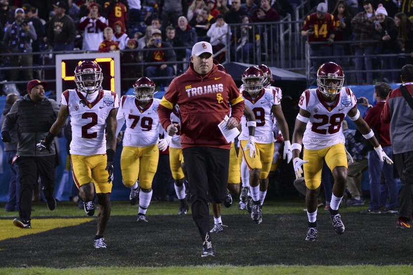 USC football coach Clay Helton leads his players onto the field before a game.