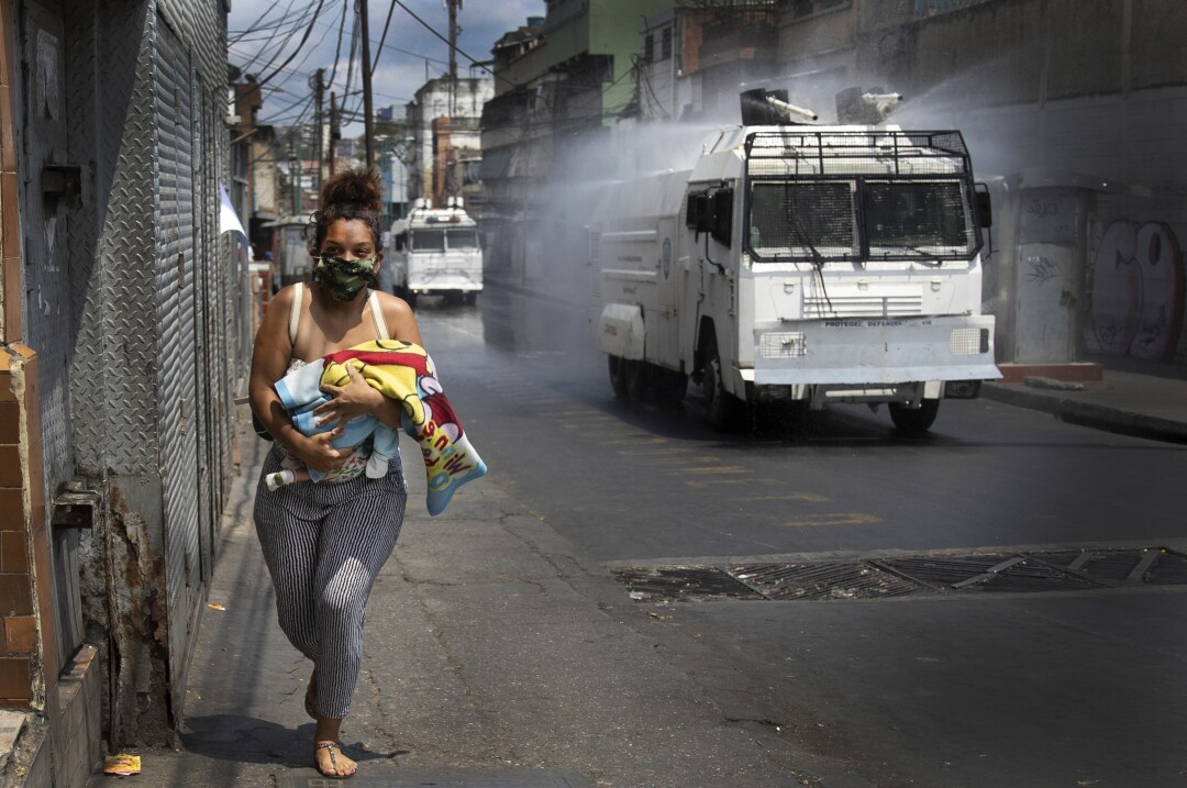 A woman with a baby runs from a truck spraying disinfectant in Venezuela.
