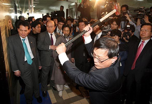 An opposition lawmaker takes a sledgehammer to the door of a conference room in South Korea's National Assembly building in an attempt to prevent members of the ruling Grand National Party from submitting a bill to ratify a free-trade deal with the U.S. The ruling party, whose members barricaded themselves in the room, managed to formally put the bill on the agenda. Seoul and Washington signed the trade deal in June 2007, but lawmakers from both countries have yet to ratify it.