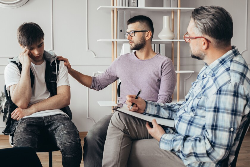 Young man in glasses comforting his depressed friend during meeting with counselor