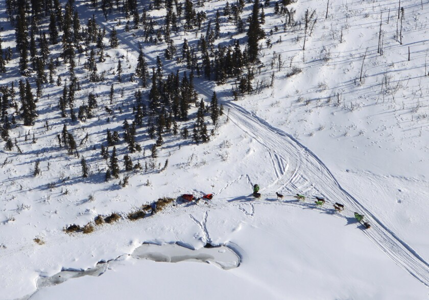 Ryan Redington, right, with his team in harness, stops near a team bedded down near the trail as the Iditarod Trail Sled Dog Race headed toward the Rohn checkpoint Saturday, March 13, 2021. (Zachariah Hughes/Anchorage Daily News via AP, Pool)