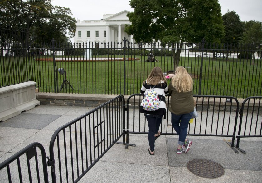 "Jenna Scheidt of Fairfax, Va., left, and Abby Loss of Eau Claire, Wis., lean against a temporary barrier along Pennsylvania Avenue in front of the White House in Washington, Friday, Oct. 3, 2014. For sightseers looking for a glimpse of the White House, an iron security fence is now part of their photographs. In the past two weeks, ""temporary"" barriers have been installed to push the public back from the gate after an intruder jumped the fence and ran inside the executive mansion. (AP Photo/Carolyn Kaster)"